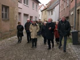 Altbürgermeister Roland Metz und die Exkursionsteilnehmer in der  Goldgasse in Arnstein